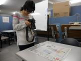 実習生さんが教材作成中です!一眼レフを両手に、新聞をパチリ!